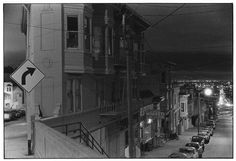 San Francisco street at Night; view from top of hill with building in foreground.