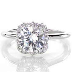 Jasmine - Our Jasmine design features a 1.50 carat center stone delicately set within four prongs. The square halo holds diamonds set in the French style with tiny hand cut double prongs. The piece is dramatically uplifted by a marquise shaped pierced design that proudly holds the halo in place.