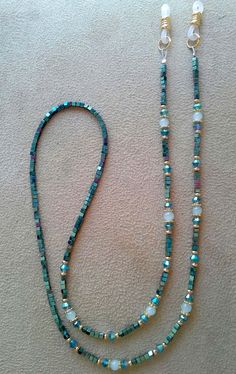 This chain is done with 2mm Green Iris coated natural hematite beads. There are Indicolite AB crystals with 4mm Amazonite Balls with gold plated spacers.. This is an elegant eyeglass chain and will make all those glasses look so beautiful either on your face or hanging down. It is one of the