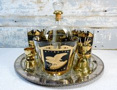 This set consists of 5 vintage hi ball glasses with a gold and black Eagle on a crest design. They are 5½ inches tall and 2¾ inches wide and in very good condition. Love that it has the matching glass ice bucket. Perfect for serving ice at your next party. It is 5 inches tall and 6 inches wide and in very good condition.