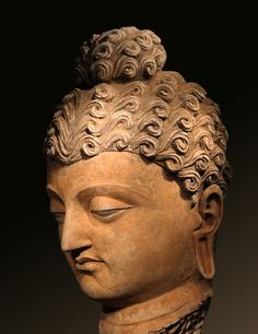 Head of the Buddha. Afghanistan, circa 2nd Century. Stucco and Pigments. 22 inches (55.9 cm).