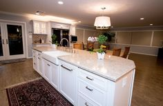 StarMark marshmallow cream cabinetry, Silestone Quasar and Kohler biscuit apron front sink