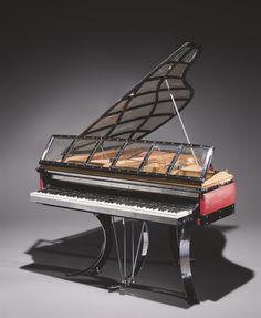 Poul Henningsen (1894-1967) pour Andreas Christensen Piano quart de queue 'Mira Flygel',1931 Le couvercle supérieur et le pupitre composés de plaques en perspex serties dans une monture quadrillée en métal chromé,la table d'harmonie laquée or,l'enveloppement du cadre gainé de cuir rouge souligné de bois laqué noir,les touches en ivoire et ébène,la lyre à deux pédales,reposant sur trois pieds courbes en lame d'acier chromé,terminés par trois patins circulaires H:94 cm. L:141,5 cm.Prof 152 cm