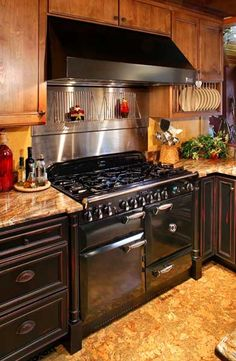 A black Aga Legacy range and black range hood give the kitchen old-fashioned charm. The cabinets, which are painted black over red with a distressed, rub-through finish, add to the appearance of age.