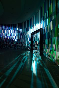the colorful glass panes reflect saturated hues within the interior of the church  the grey tiling on the floor echos the shadow created by the panel