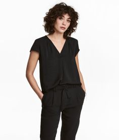 Black. Loose-fit, short-sleeved blouse in crinkled woven fabric with a gathered V-neck at front. Rounded hem.