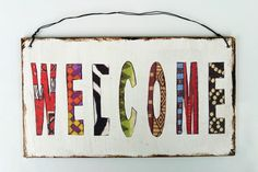 *Welcome*  In einem afrikanischem Muster - für die Kunstraub Aktion Nr. MusterHäuser hergestellt.    Zum Aufhängen wurde das Dekoschild mit e...