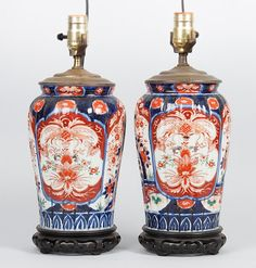 Pair of Japanese Imari porcelain vase lamps  late 19th century; each vase with fanciful garden vignettes, mounted on oriental style wood base, with carved hardstone pendant finials, 14 in. H.