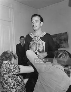 Artist Salvador Dali putting on costume for his party 'Night in a Surrealist Forrest.' Guests had to dress as bad dreams. Event was held at Bali room of Hotel Del Monte. Monterey, California 1941
