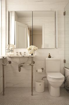 Beautiful compact bathroom design with linear brick marble tiled walls. A modern mirrored medicine cabinet is paired with two tubular wall sconces at either side. A singular washstand with chrome base and marble countertop sits next to the window. The floor is covered in a mini Calcutta marble brick tile with a contrasting dark gray grout.