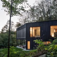Montreal architecture firm Atelier General has created a two-storey black residence on a hillside in Quebec, with a main living room…
