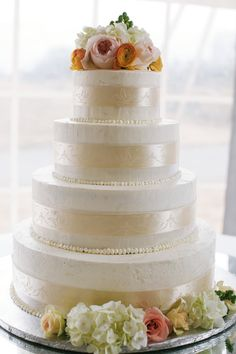 Elegant wedding cake idea - white four-tiered fondant-frosted cake with ivory ribbon detail + bright flowers {Lara Kimmerer | photographer}