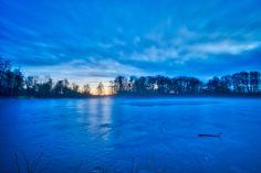 Der Aueweiher in Fulda im Winter. Der Sonnenuntergang hat ein schönes Blau auf die Eisfläche gezaubert.