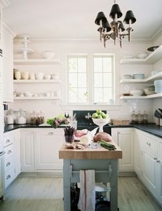 White kitchen, black countertops, dusty blue island with natural wood top, and open shelving - yes please
