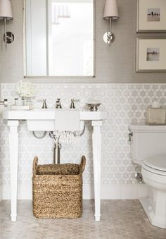 Dazzling white bathroom with glass and mother-of-pearl tile from Oceanside Glasstile cover the walls in a second powder room, and play off of the geometric stone flooring. Coastal sisal wallpaper from Thibaut warms up the space. Check out the rest of this sophisticated home at ElleDecor.com | Designed by Alice Lane | Featured in @elledecor