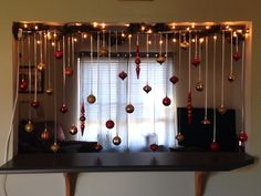 Easy ornament decoration. All you need is a tension rod, ornaments and ribbon. To make it pop with that perfect Christmas magic add the lights.