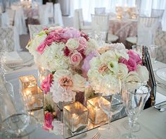 Sheer elegance is created with floral arrangements surrounded by four gold votives atop a mirrored table.