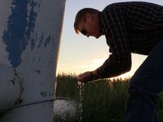 Jay Garetson lets water run into his hands from a well