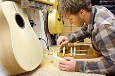 Woodworker Building Guitar in Workshop Stock Photography