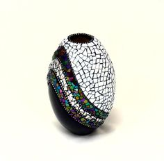"""""""Bejeweled"""" is a unique beautiful artisan piece of jewelry for your home. This is a black ceramic mosaic vase partially done in white stained glass and adorned with a sweeping wave of purple-green-blue iridescent glass, mirror, and silver finished bead chain. Finished with black grout sealed in a matte finish. Measures approximately 8"""" H x 5"""" W and has been signed by me (the artist)."""