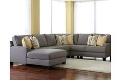 Indulge in modern relaxation with the inviting scale of a Chamberly 4-piece sectional. Sleek lines and legs give the profile a sophisticated look, while low track arms, supportive cushioning and soft feather-filled pillows create a place to lounge. Cool earth-tone upholstery fits in with contemporary color schemes and is easy care.