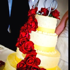 Yellow Wedding Cake with Red Roses wrapped around! Gorgeous!