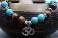 What you see is what you get - this is the only one of this bracelet I will make! Get it before its gone! - 8mm turquoise magnesite stone beads. - 8mm tigers eye stone beads. - Silver tone Om charm and accents. - 6 Inches un-stretched (approximately). This bracelet best fits people with a small frame. - Ships from Canada.  The turquoise and tigers eye combination is getting pretty popular and I see why - its so adorable. This piece is completed with an Om charm, making this perfect for…