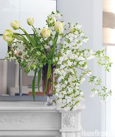 An asymmetrical arrangement of tulips and pear blossoms appoint the mantle in the living room of a Park Avenue apartment.   - HouseBeautiful.com