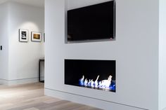 "Modern fireplace with custom metal firebox and 36"" BioFlame bio-ethanol linear burner, recessed base trim, Samsung LED TV with pivoting wall mount, and wide-plank European white oak floors in Washington, DC."