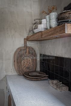 concrete worktop and concrete wall with reclaimed wooden shelving
