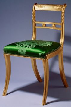 Tatham & Bailey Chair  1813. Gilt wood, silk damask. A set of eighty-eight dining-chairs, each with a gently curved back and uprights, the top rail with stylised flowers and husks above a double bar splat joined by two rosettes; sabre legs. Variously covered in red, green or blue foliate silk damask. Ball Supper Room, Buckingham Palace.