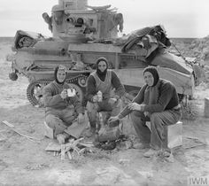 The British Army in North Africa.The crew of a Light Tank Mk VIB cook their Christmas dinner besides their vehicle, 31 December 1940.