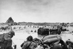 Utah Beach, Infantry troops arrive at Green Beach (Saint-Martin-de-Varreville) wade  ashore, and prepare to move inland. Antilanding obstacles have already been cleared, but at this stage, shortly after the initial landings, there is still little evidence of organization on the beach for the subsequent build-up.