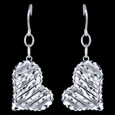 Silver earrings, heart Silver earrings, Ag 925/1000 - sterling silver. Dangle earrings. Rhodium-plated. Precisely crafted three-dimensional heart with special surface finish, so called diamond cut, to increase shimmering effect. Heart dimension approx. 20x13x4mm excluding enclosure, height of circles above the heart approx. 9mm. Price per pair.