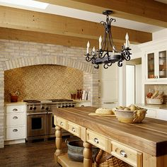 Brick shapes this range nook, complementing the kitchen's exposed rafters, wood island, wood flooring, and abundant natural light.