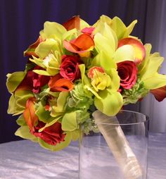 Green orchid bouquet with touches of red roses. #wedding #flowers #bouquet