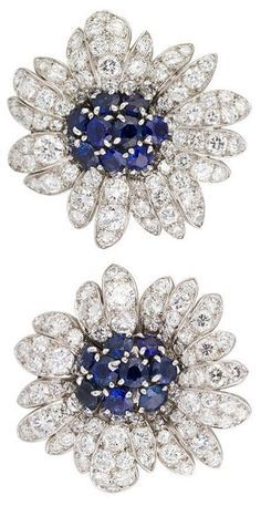 Van Cleef & Arpels diamond, sapphire, and platinum earrings.  France,  1950s-60s.  Rare and important platinum set diamond and sapphire earrings, circa 1950s-60s by Van Cleef & Arpels. They feature a clip back mechanism with a retractable claw, so that the earrings can easily convert into brooch clips. Earrings have approx. 8.0cts of very high quality brilliant cut diamonds adorning the petals, and rich blue sapphires pave set at its center of approx. 3.0cts total weight.