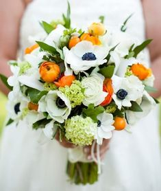 Orange ranunculus and kumquats burst against a feisty grouping of dark-centered anemones and mini viburnum.