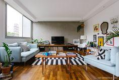 Sala de estar tem parede de cimento queimado, sofá azul claro e tapete listrado.
