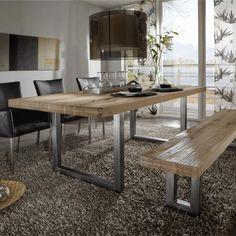 une table en bois clair avec des pieds métalliques dans la salle à manger