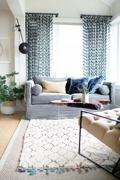 Living room with a gray sofa, printed curtains, and layered area rugs