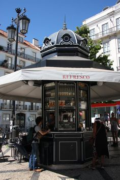 Designers, antique shops, chic bars and nightspots: The stylish districts of Chiado and Bairro Alto expose Lisbon at its quintessential best. Kiosk Store, Mall Kiosk, Bude, Halle, Urban Ideas, Tour Around The World, Kiosk Design, Shopping Malls, Shop Fronts