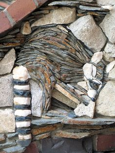 """""""Rockelle Raccoon is turning over a rock in a stream."""" ... part of a stone mural wall at Bass Lake, CA by Pierson Masonry;  made with ledger stone, brick, quart, and granite"""