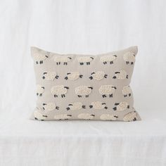 """Our sheep pillow is Fair Trade from India-- grey textured linen is adorned with beautiful wool sheep. 12 x 16""""."""