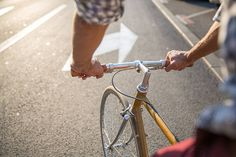 Closeup on man's hands on bicycle handlebar by Jovo Jovanovic for Stocksy United