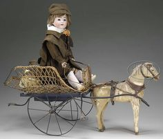 Antique boy doll riding a toy horse pulled toy wagon .