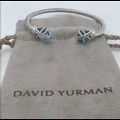 David Yurman Blue Topaz & Diamonds Cable Bracelet David Yurman Sterling Blue Topaz & Diamonds Cable Wrap Bracelet  Price is negotiable just no low ball.  Hallmark:  DY. 925  Size 4mm Measurment: See photo above. topaz size 10×10 mm Diamonds: .05cts  Pouch is not included for picture purposes only. David Yurman Jewelry Bracelets