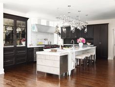 The double refrigerator with bottom freezers has mirror-and-wood panel fronts for furniture styling. - Traditional Home®