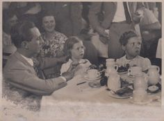 Hilde, Helga, and their father having a meal at some public occasion, c. 1937