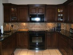 Brown kitchen cabinets with dark countertop and lighter colored tile backsplash and floors.